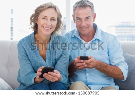 Happy couple using their smartphones looking at camera at home in the living room