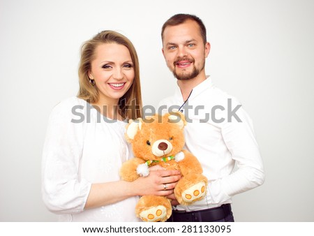 Happy couple waiting for a baby, handsome guy with his beautiful pregnant wife  with a teddy bear, love concept - stock photo