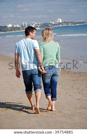 Happy couple walking along beach - stock photo
