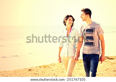 happy couple walking along the beach at sunset - stock photo