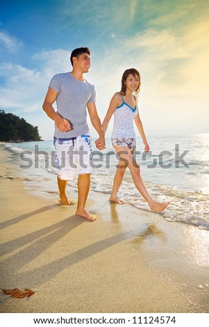 happy couple walking along the sunset golden sand beach
