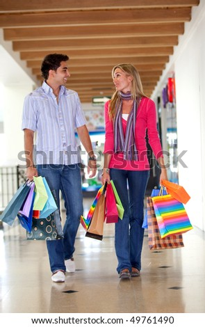 Happy couple walking at a shopping center and smiling - stock photo
