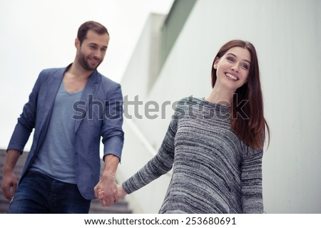 Happy couple walking hand in hand in an urban environment with the young woman leading the way with a friendly smile - stock photo