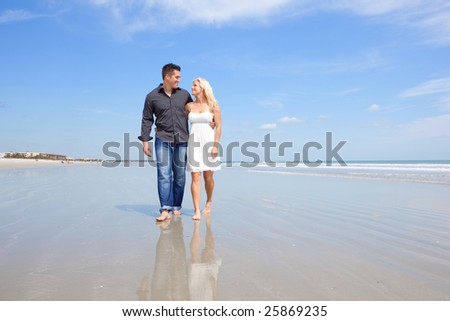 Happy couple walking on a beach. - stock photo