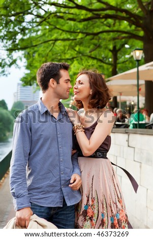 happy couple walking on a street and hugging - stock photo
