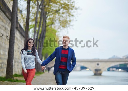 Happy couple walking on the bank of the Seine in Paris. Tourists enjoying their vacation in France. Romantic date or traveling couple concept - stock photo