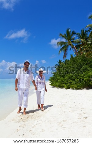 Happy Couple walking on the Beach  - stock photo