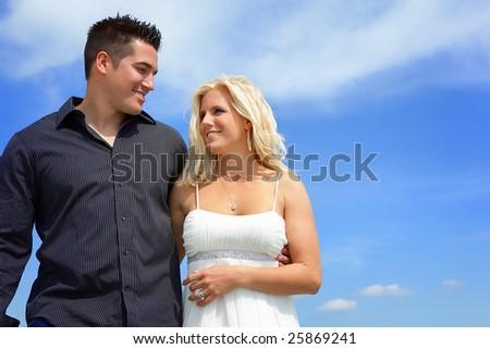 Happy couple walking. Opposite blue sky. - stock photo