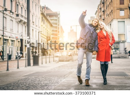 Happy couple walking outdoors on the streets - Two tourists visiting a city - Lovers having a romantic walk - stock photo