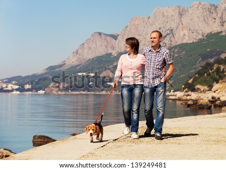 Happy couple walking with beagle puppy at the seacoast - stock photo