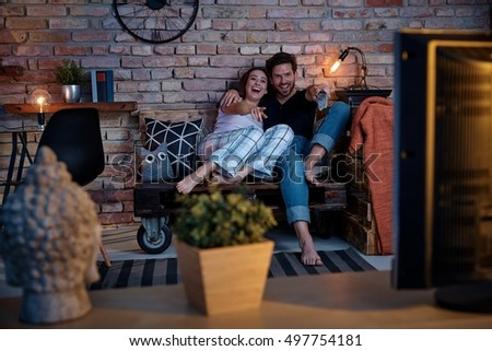 Happy couple watching comedy at home on tv, sitting on pallet furniture.