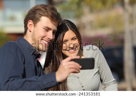 Happy couple watching media in a smart phone outdoors with an urban background - stock photo