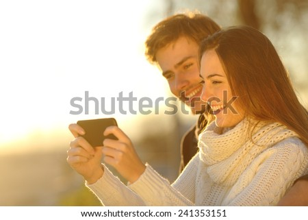 Happy couple watching media videos in a smart phone at sunset on the beach - stock photo