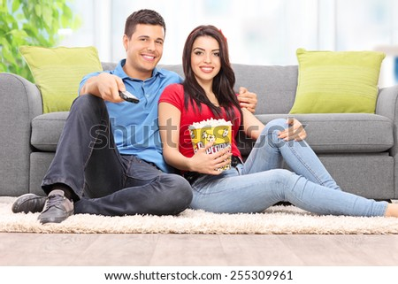 Happy couple watching TV and eating popcorn at home