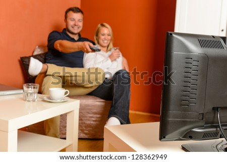 Happy couple watching tv evening relaxing changing channels remote control - stock photo