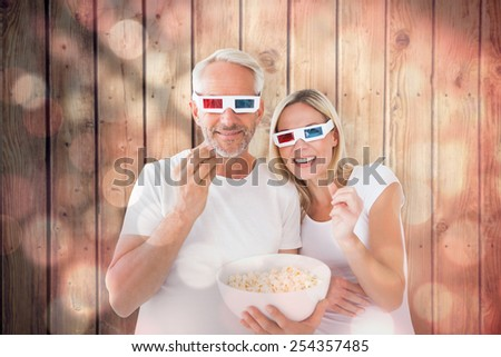 Happy couple wearing 3d glasses eating popcorn against light circles on black background - stock photo