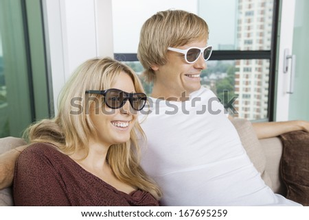 Happy couple wearing 3D glasses while sitting on sofa at home - stock photo