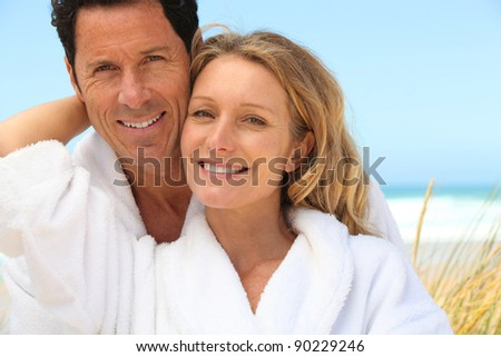 Happy couple wearing dressing gowns at the beach - stock photo