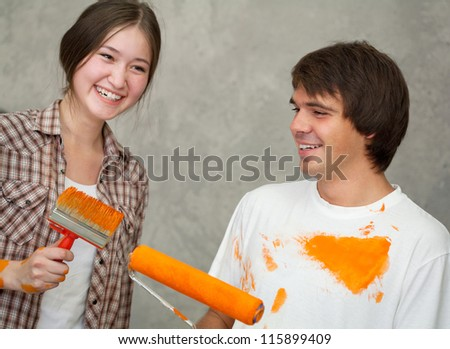 Happy couple while painting room - stock photo
