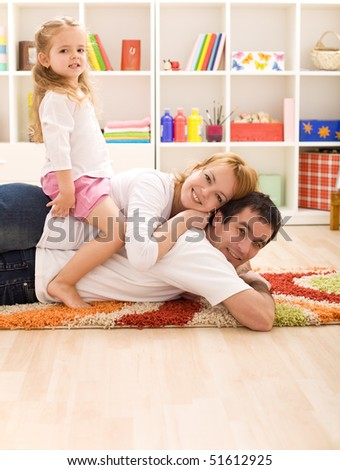 Happy couple with a child in the kids room having fun - stock photo