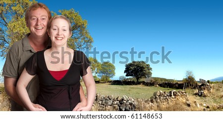 Happy couple with a country enclosure on the background - stock photo