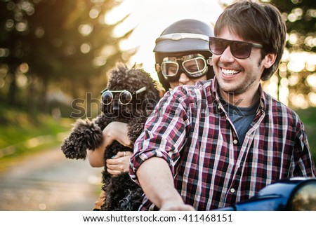 Happy couple with a dog on a scooter at summer vacation - stock photo
