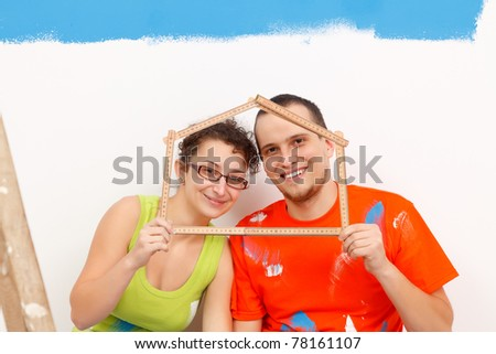 Happy couple with a folding rule in their hands in form of a house