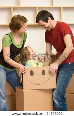 Happy couple with a kid unpacking in their new home, with lots of cardboard boxes - stock photo
