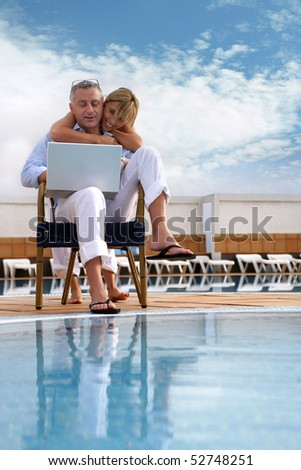 Happy couple with a laptop computer next to a swimming pool - stock photo