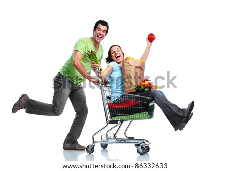 Happy couple with a shopping cart. Isolated over white background.