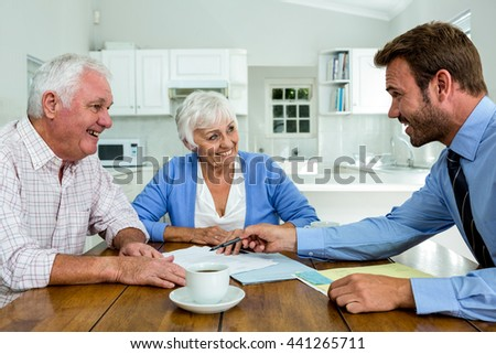 Happy couple with agent while sitting at table in home