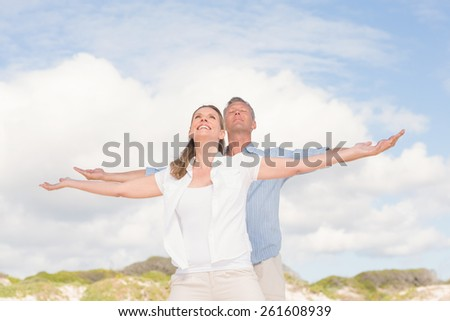 Happy couple with arms outstretched at the beach - stock photo