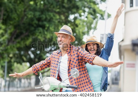 Happy couple with arms outstretched riding moped in city - stock photo