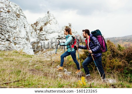 Happy couple with backpacks hiking uphill with rocks in backgorund - stock photo