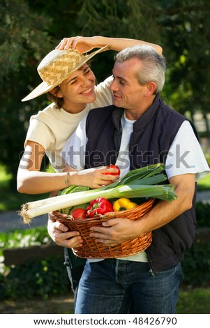 Happy couple with basket of vegetables