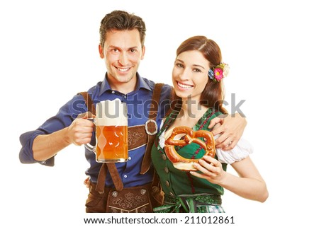 Happy couple with beer and pretzel at Oktoberfest in Bavaria - stock photo