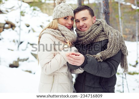 Happy couple with Bengal light celebrating winter holiday in natural environment