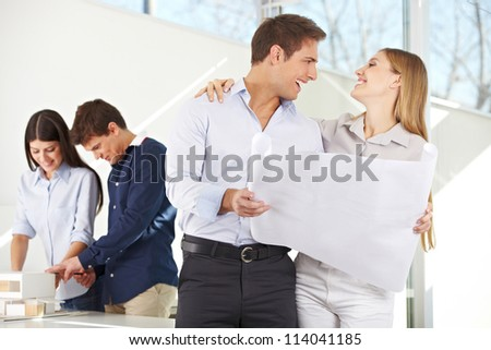 Happy couple with building plan for their new house in architecture office - stock photo