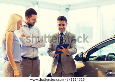 happy couple with car dealer in auto show or salon - stock photo