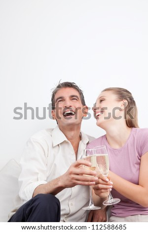 Happy couple with champagne flutes, laughing.