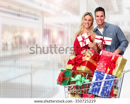 Happy couple with Christmas gifts over shopping mall background.