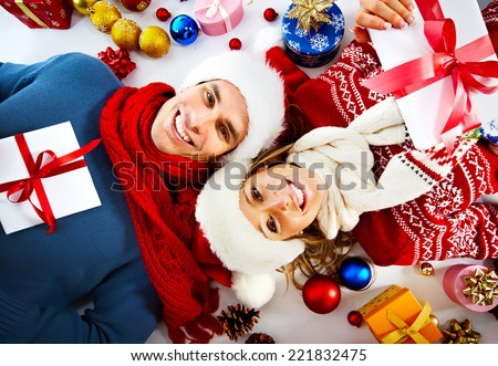 Happy couple with christmas gifts relaxing at home - stock photo
