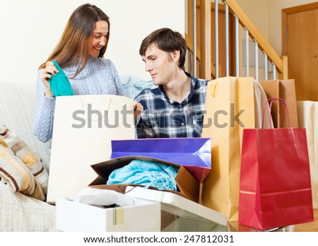 Happy couple with clothes and shopping bags in home interior