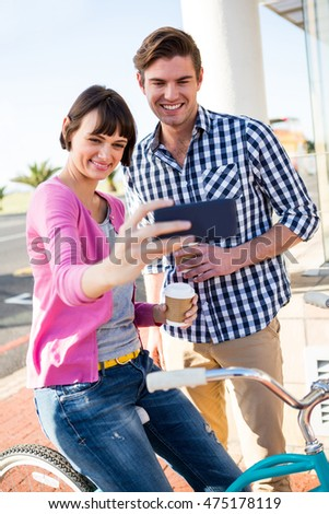 Happy couple with coffee cups taking a selfie
