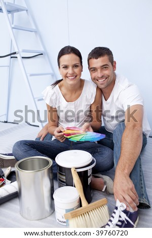 Happy couple with color samples to paint new appartment - stock photo