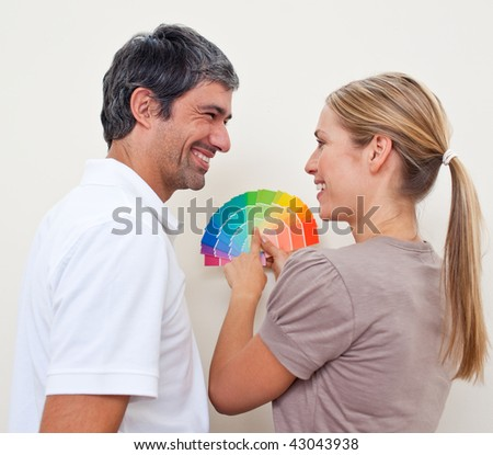 Happy couple with color samples to paint their new appartment - stock photo