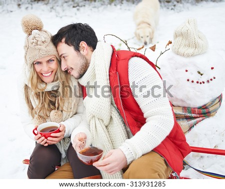 Happy couple with dog drinking tea in winter sitting on a sled - stock photo