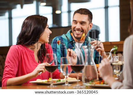 happy couple with friends eating at restaurant - stock photo