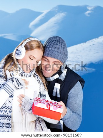 Happy couple with gift, people outdoor at winter snow mountains, young man giving present to beautiful woman, Christmas vacation holidays, love concept - stock photo