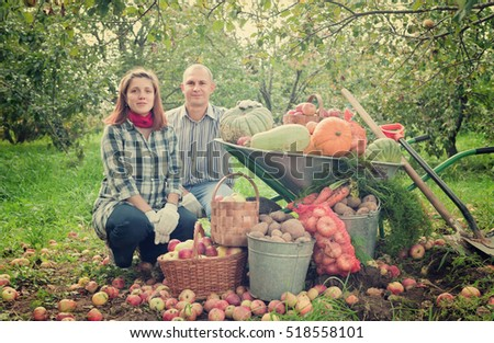 Happy couple with  harvested vegetables in garden